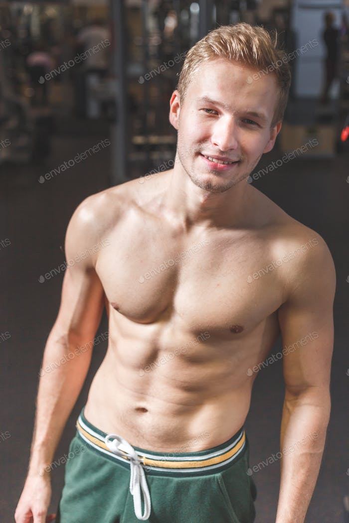 Sexy portrait of a young muscular male model with great happy smile in the gym