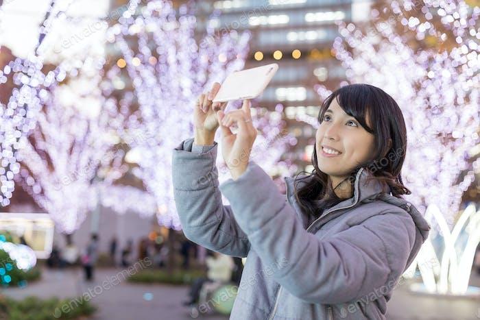 Junge Frau fotografiert mit Weihnachtsdekoration