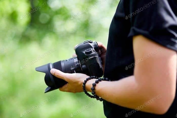 Mann Fotograf mit einer Fotokamera in der Hand im Freien