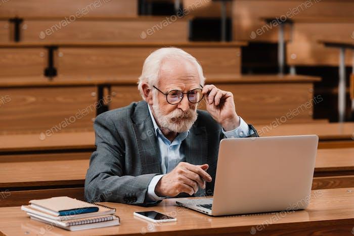 grey hair professor looking at laptop