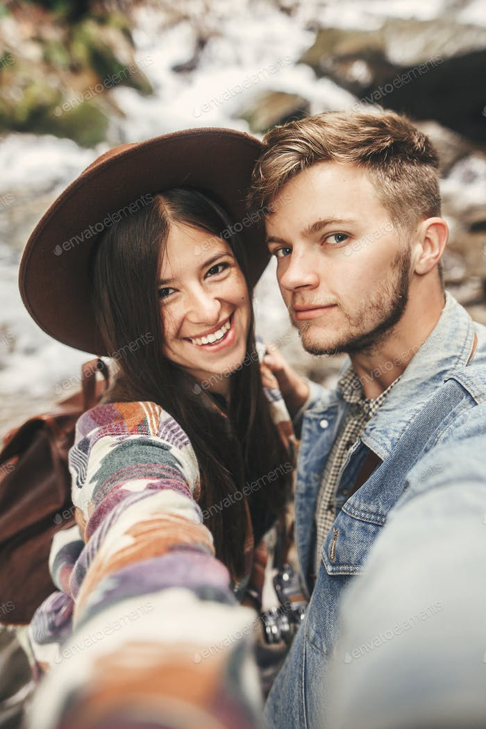 Happy hipster couple making selfie and smiling at waterfall in forest mountains
