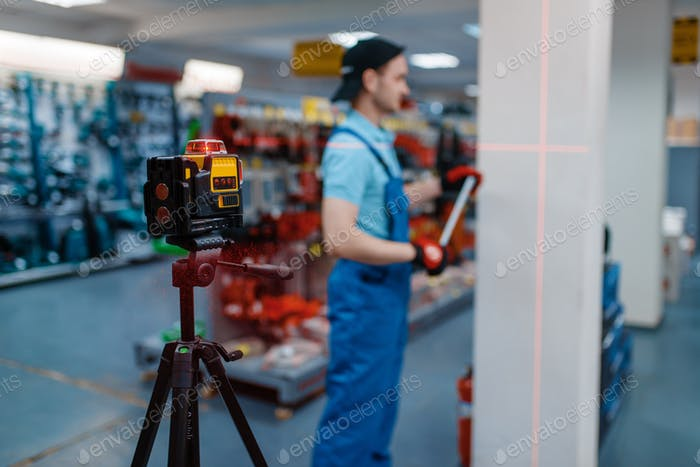 Worker testing laser level on tripod in tool store