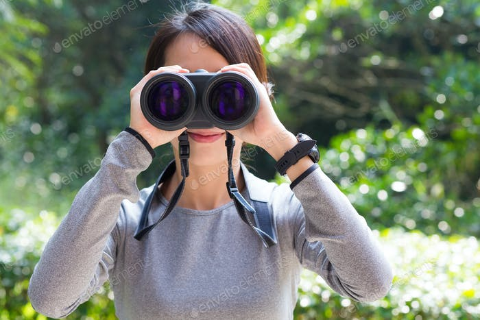 Asian woman use of the binocular in jungle
