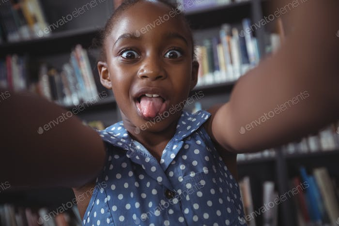 Happy girl making face in library