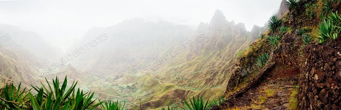 Panorama of Xo-Xo valley surrounded by harsh mountain peaks. Steep walk path covered by yucca plants