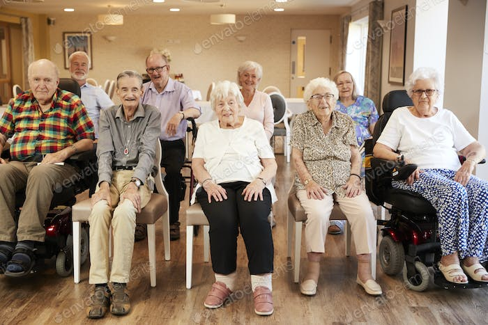 Portrait Of Senior Residents Of Retirement Home Sitting In Lounge