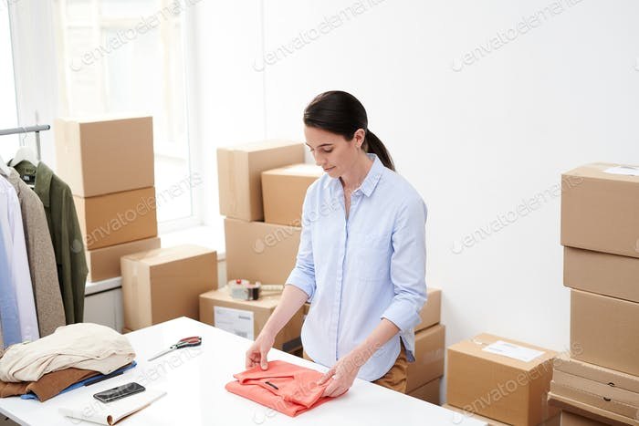Young female online shop worker folding red pullover for packing