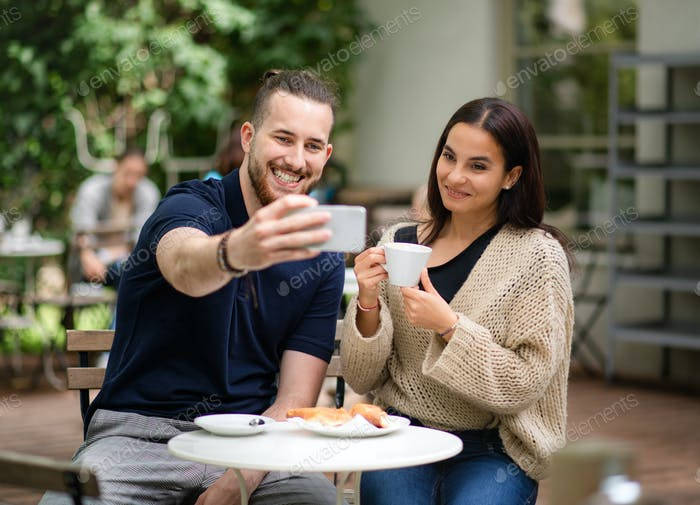 Happy young couple sitting outdoors in cafe, taking selfie by smartphone