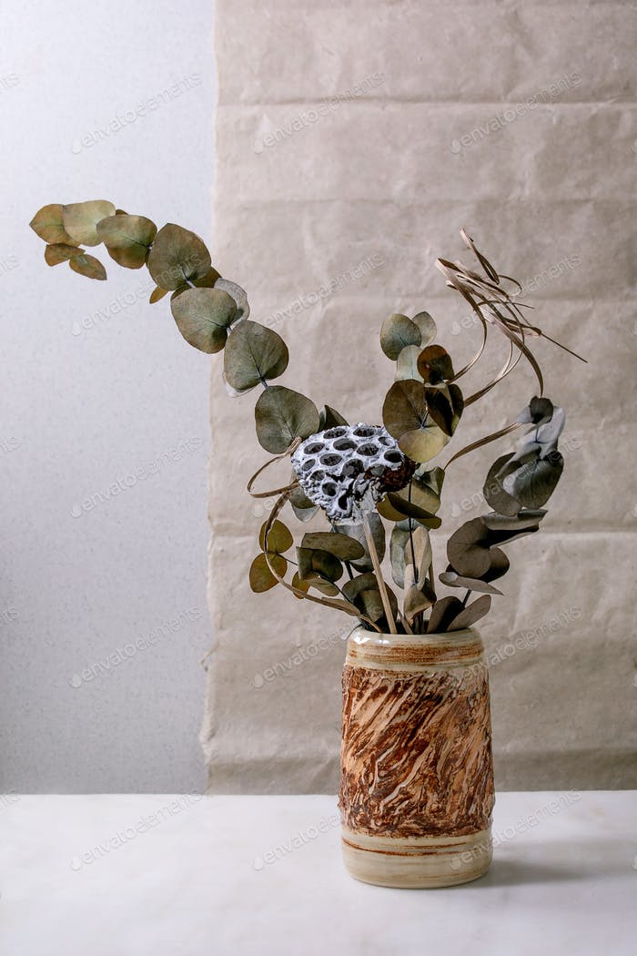 Dry flowers and twigs branch in ceramic vase