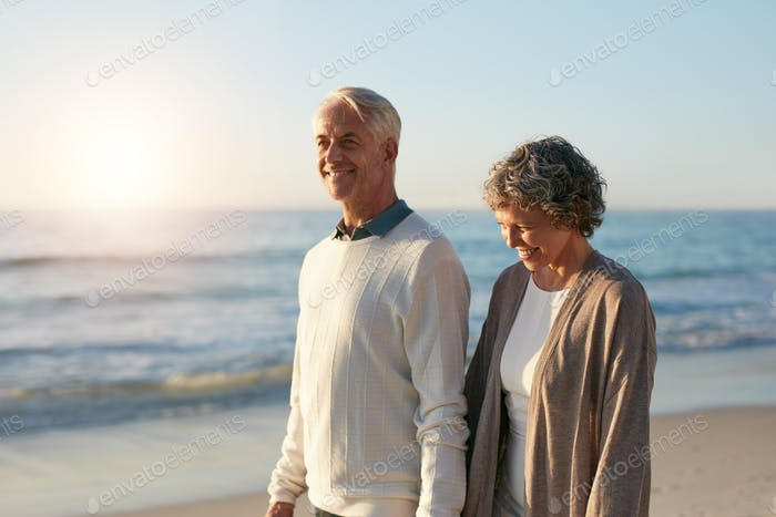 Happy mature couple walking along the beach