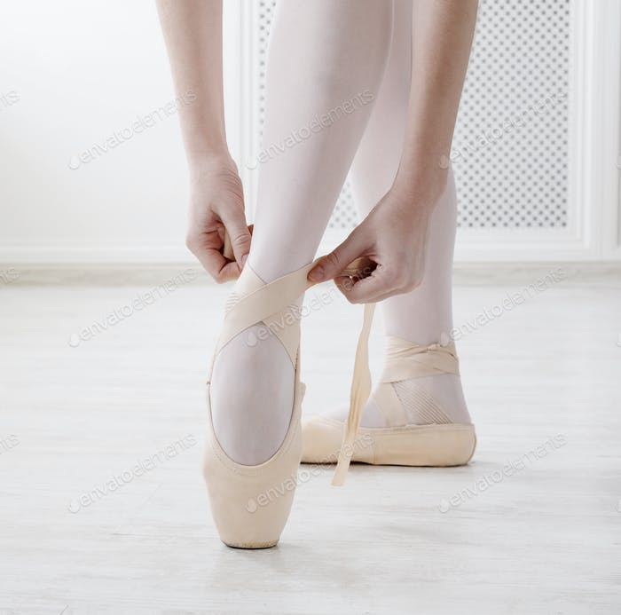 Closeup legs of ballerina puts on pointe ballet shoes