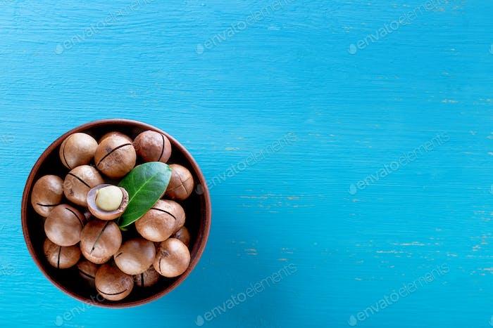 Australische Macadamia-Nüsse mit Blatt in Platte auf blauem Holzhintergrund