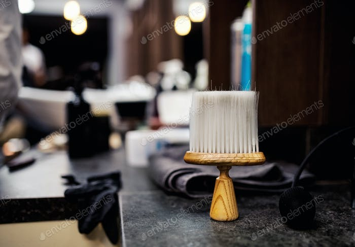 A hair dust brush and other tools in hair salon for men, barbershop interior.