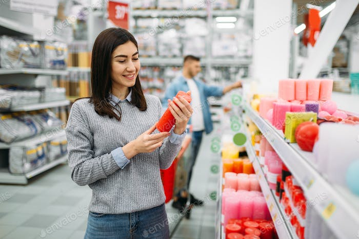 Couple choosing candles in supermarket, shopping