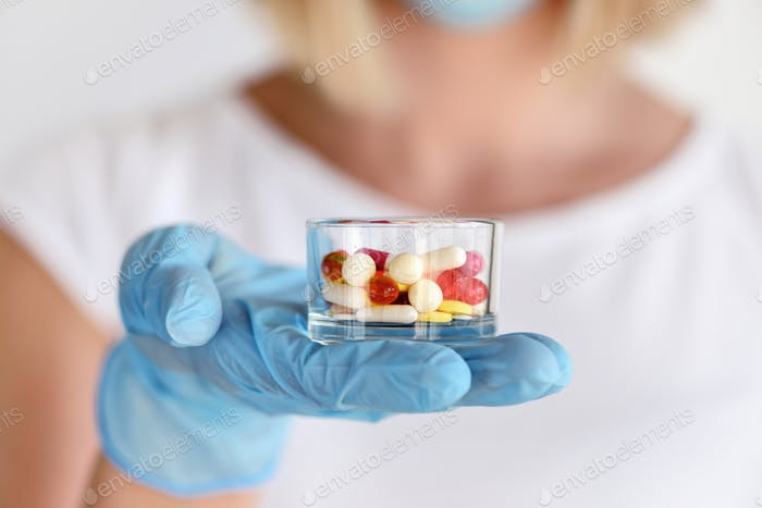 Hand of a or nurse in gloves holds a glass with pills to be taken to her patient