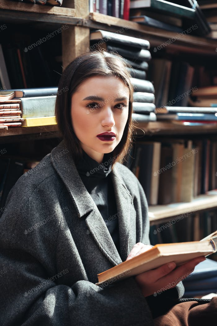 Young girl in coat holding book in an old library