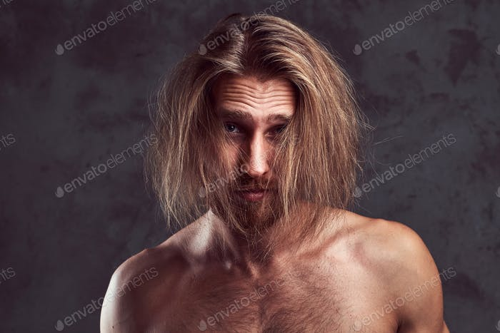 Portrait of shirtless redhead handsome man, isolated on dark background.