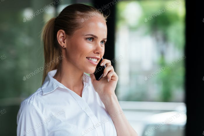 Cheerful young businesswoman standing and talking on mobile phone