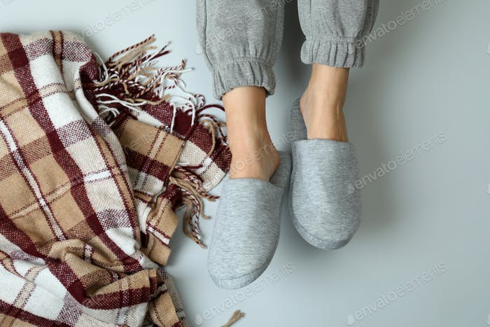Female legs in gray slippers on gray background