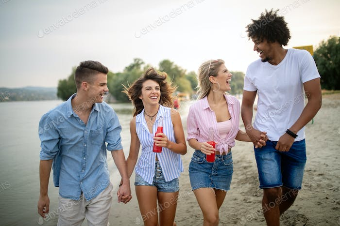 Group of friends having fun on the beach. Summer holidays, vacation and people concept