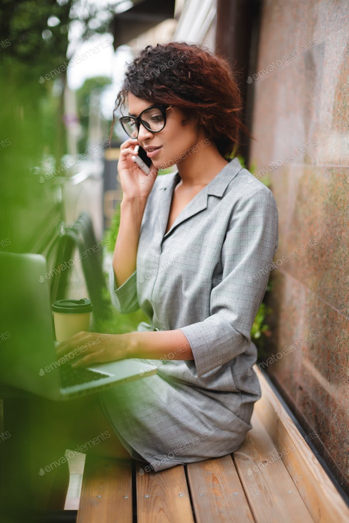 African American Mädchen in Brille sitzen auf Bank und sprechen auf Handy während der Arbeit auf Laptop