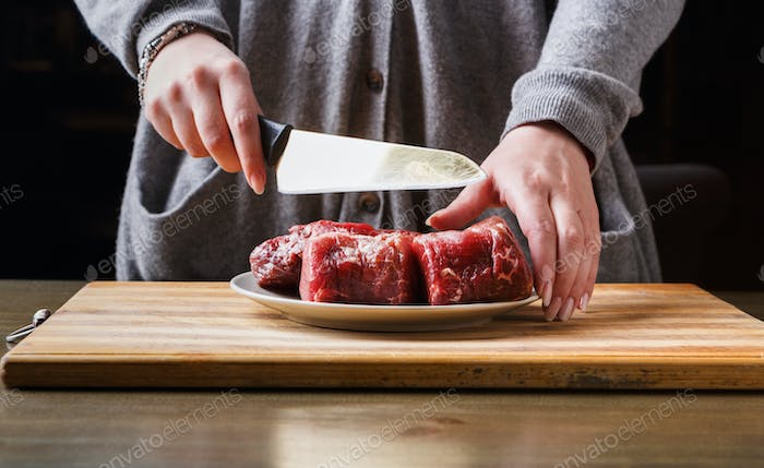 Preparing filet mignon. Female hands cutting meat for cooking