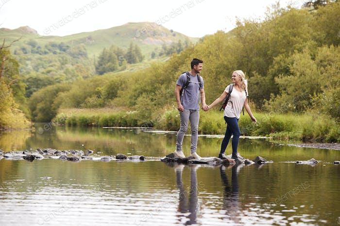 Paar überqueren Fluss während Wandern in UK Lake District