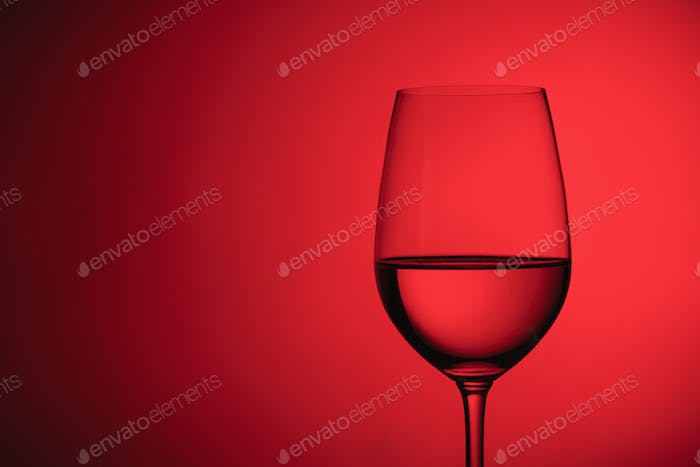 Glass of wine over a red background