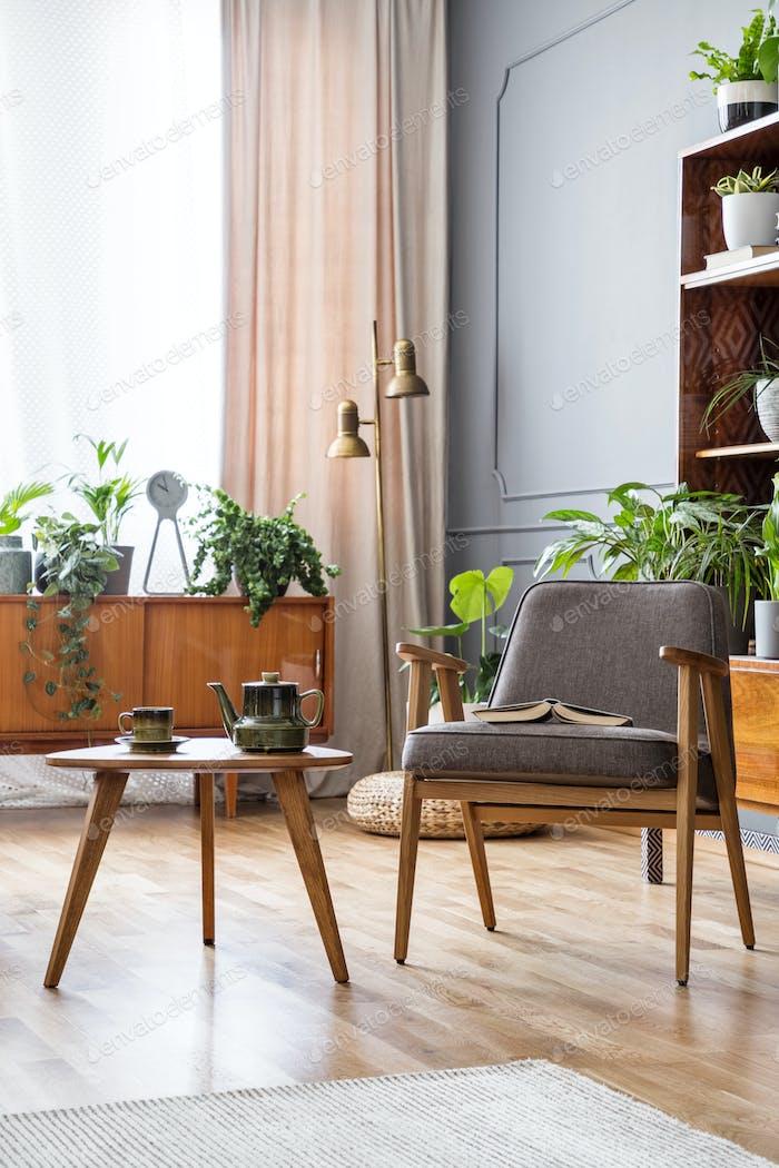Holztisch neben grauen Sessel in Vintage-Wohnzimmer interi