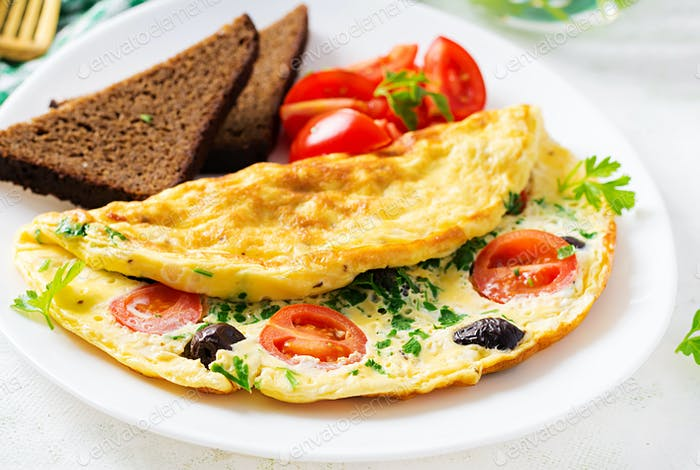 Omelette with tomatoes, black olives, cottage cheese and green herbs