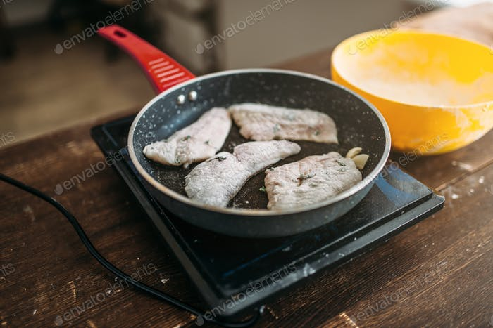 Frying pan with fish slices, seafood cooking