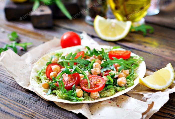 Vegan tacos with guacamole, chickpeas, tomatoes and arugula. Healthy food. Useful breakfast