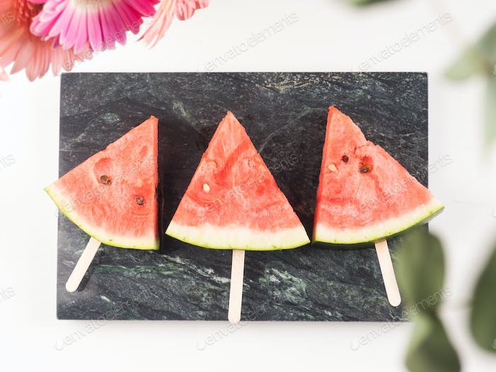 Watermelon slice popsicles on marble tray