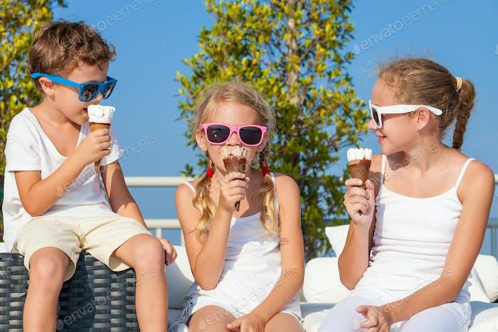 three happy children eating ice cream near swimming pool at the