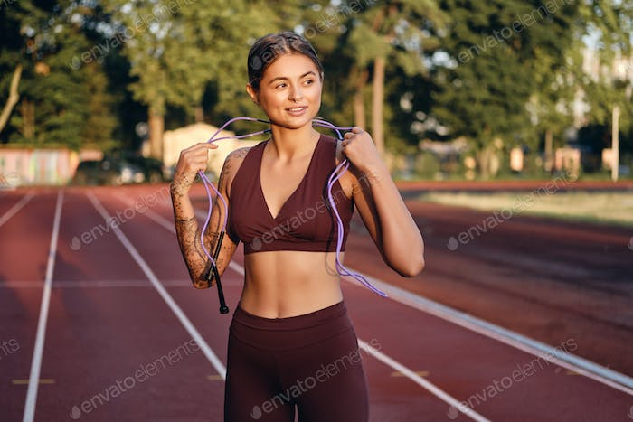 Attractive fit girl in sportswear with skipping rope on neck dreamily training on city stadium