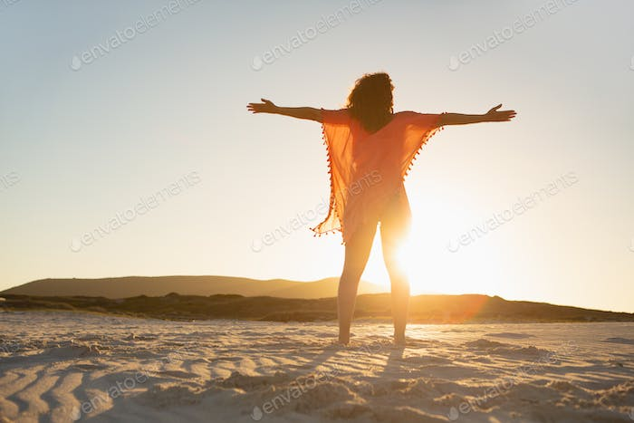 Low angle view of mixed race woman with arms stretched out standing on beach in the sunshine