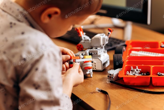 Smart boy dressed in gray shirt makes a robot from the robotic constructor at the desk in the School