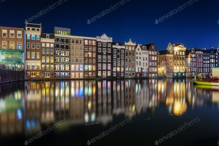 Beautiful traditional old buildings on canal in Amsterdam at nig