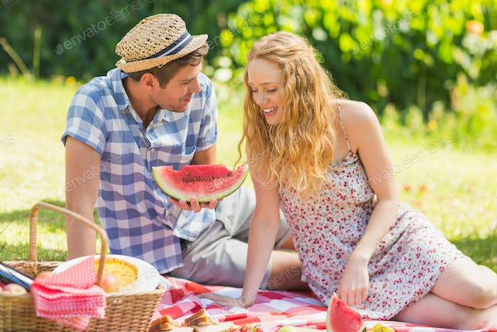 Young couple on a picnic eating watermelon on a sunny day