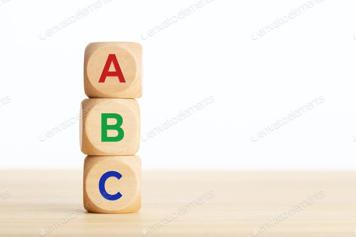 ABC letters alphabet in wooden blocks stacked on wood table