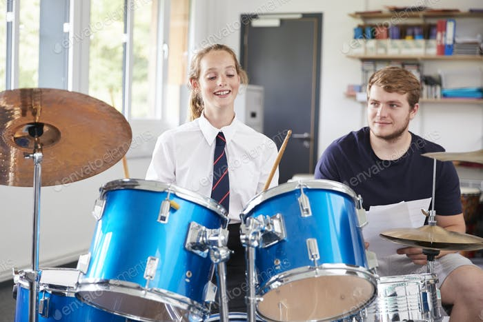 Female Pupil With Teacher Playing Drums In Music Lesson