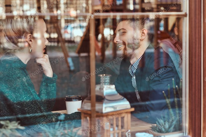 Young couple looking at each other and talking while sitting in the restaurant behind the window