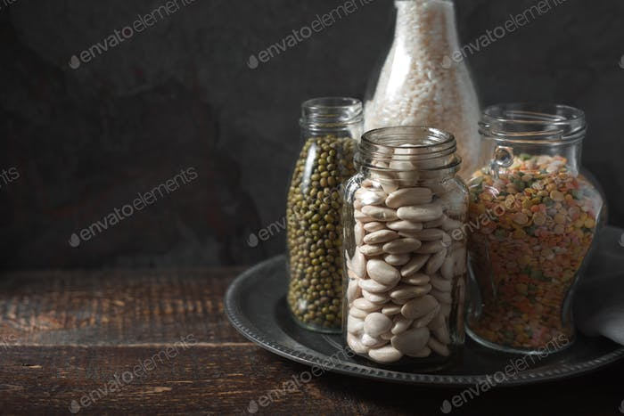 Lentils, white beans, rice in glass bottles copy space