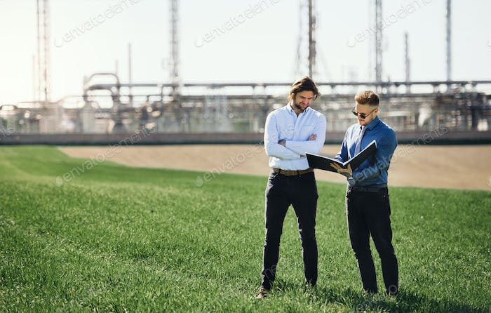 Two young engineers standing outdoors by oil refinery, discussing issues