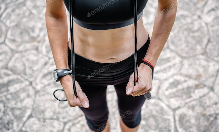 Woman posing with skipping rope in a park
