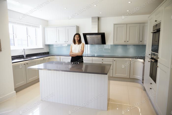 Portrait Of Female Realtor In Kitchen Valuing House