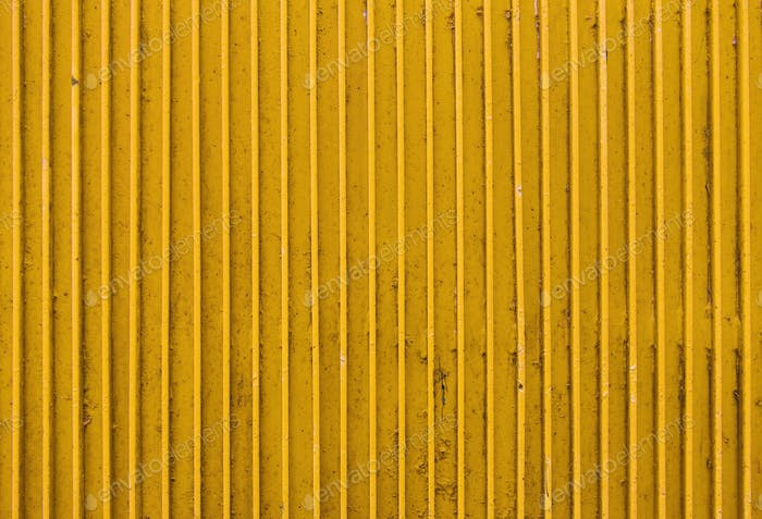 old yellow painted metal ribbed surface