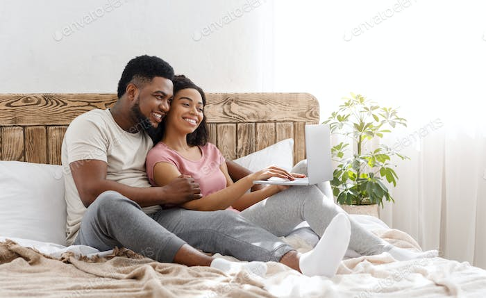 Black couple in love using laptop in bedroom at home