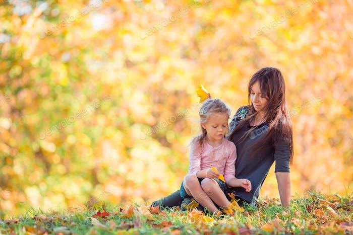 Niña con mamá al aire libre en parque en el día de otoño