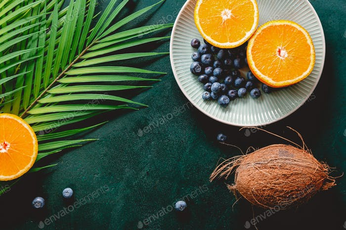 Summer flat lay with palm leaf, oranges, blueberry and coconut over dark green background.